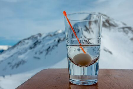 on a table stands a glass with alcohol and in the background are the snow-covered mountains