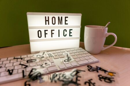 a light box with the inscription Home Office stands on a desk and in front of it is a keyboard Standard-Bild