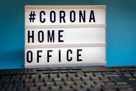 a light box with the inscription: #CORONA HOME OFFICE is behind a black computer keyboard against a blue background