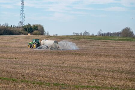 a tractor with a liquid slurry trailer fertilizes the field