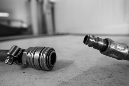 a compressed air hose with coupling is lying on the floor of a workshop