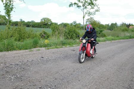 Moped rider riding a scooter on a country road Banque d'images