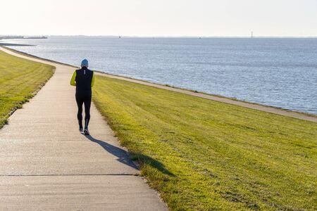 a jogger runs along a dike at the North Sea in the morning