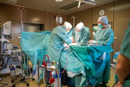 in an operating room, a caesarean section is performed by a surgical team