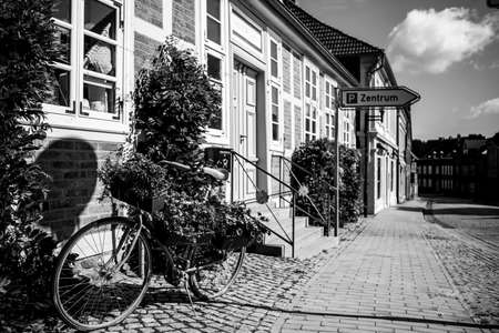 in front of an old half-timbered house stands a bicycle planted with flowers for decoration