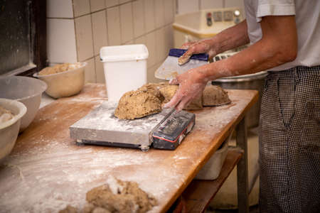 baker portions the bread dough into equally sized pieces
