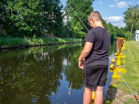 a boy stands at a canal and fishes with his fishing rod