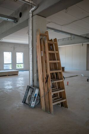 Wooden ladders leaning against a pillar in a factory building on a construction site
