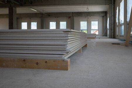 drywall panels are lying on the floor of a factory building on a construction site