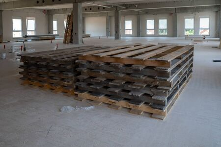 wooden pallets lying on the floor of a factory building on a construction site