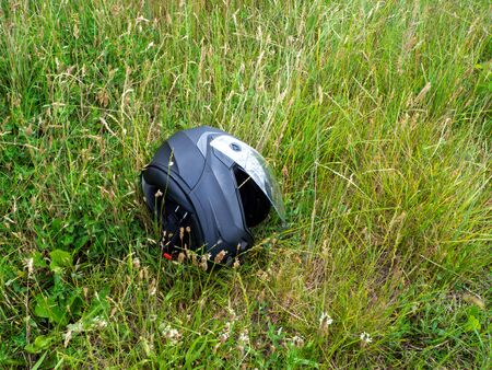 a motorcycle helmet lies with open visor in the green grass