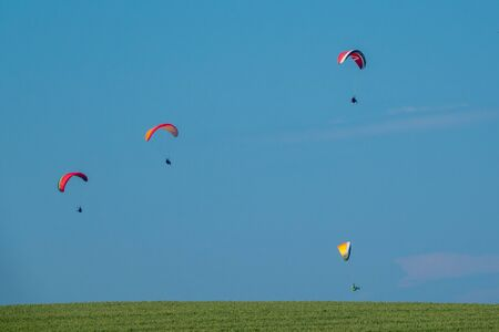 over a green field on the horizon fly different paragliders