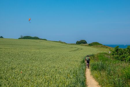 a cyclist rides along a very narrow sand path and a paraglider flies on the horizon