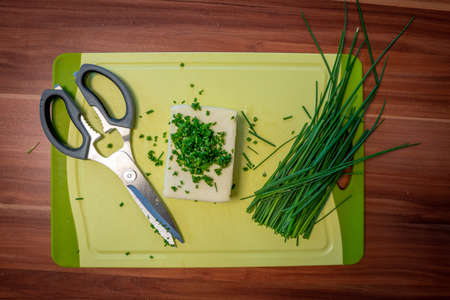 on a cutting board lie butter, chives and scissors to prepare herb butter Stock Photo