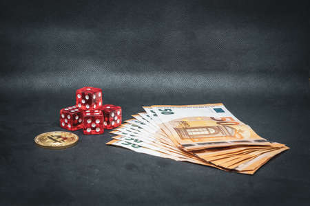 a Bitcoin coin, a pile of Euro banknotes and a few red cubes lie side by side on a dark background