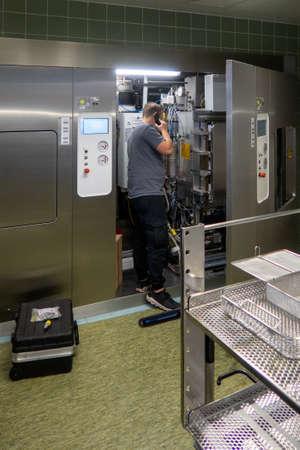 a customer service representative repairs a steam sterilizer in a hospital