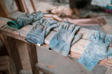 four used, dirty work gloves lying side by side on a wooden board on a construction site