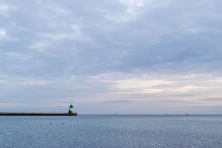 a green lighthouse stands at the end of a pier at the baltic sea