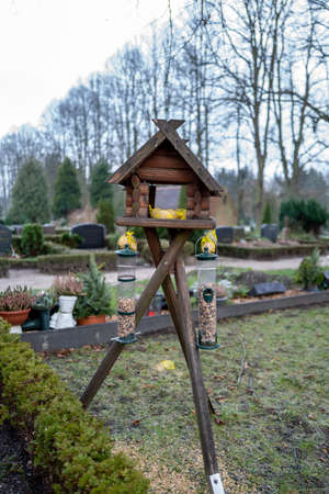 a wooden bird house filled with bird food stands on a cemetery Reklamní fotografie