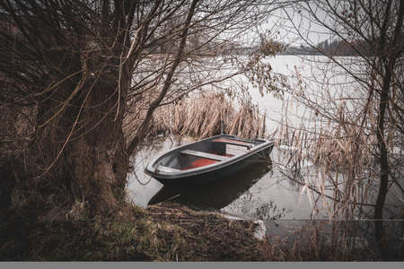 a rowing boat is moored on the shore of a frozen lake