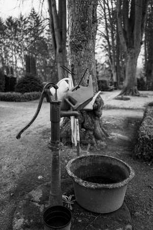 next to an old water pump stands a stand with different watering cans on a cemetery Reklamní fotografie
