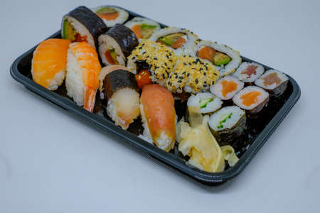 different kinds of sushi lie side by side on a black plate Reklamní fotografie