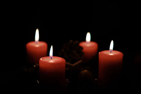 a close up of a burning red candle and the background is dark Reklamní fotografie