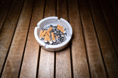 Cigarette butts lie crushed in a white ashtray standing on a wooden table Standard-Bild