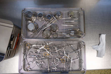 various surgical instruments lie in sieves on a work surface Redakční