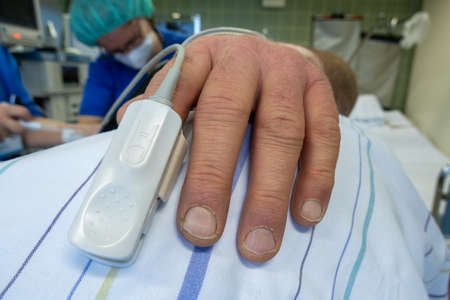 a pulse oximeter for measuring the oxygen content of the blood is attached to a patient's finger