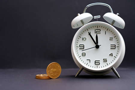 a classic white alarm clock stands next to some gold coins and the time shows 5 minutes to 12