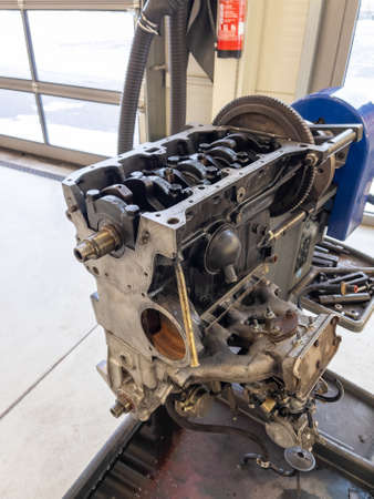 in a garage there is an opened engine block of a car
