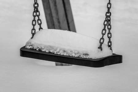 on the seat of a child swing is quite a lot of snow Standard-Bild
