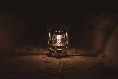 a burning oil lamp stands on a snowy path at night
