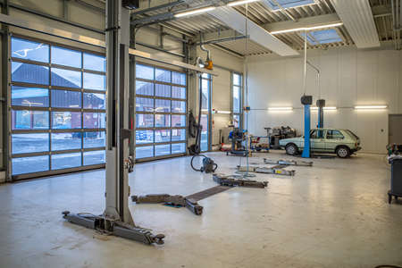 in a big empty car workshop there are some car lifts Standard-Bild