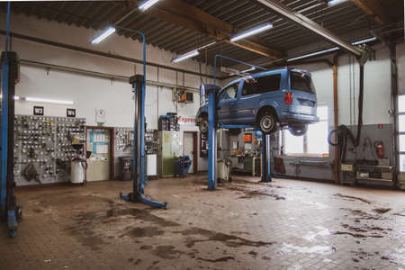 In a car workshop there are lifting platforms for repairing cars