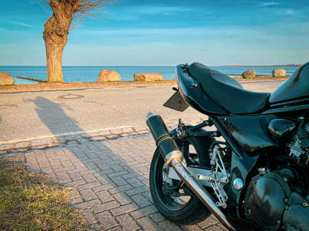a black motorcycle stands in the sunshine by the sea and the sky is blue
