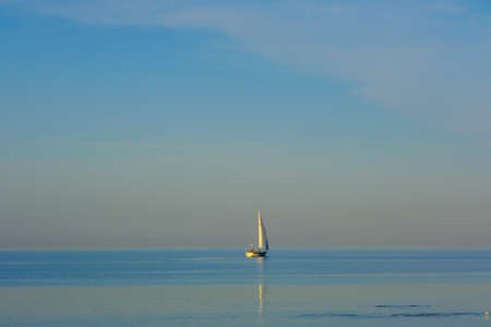 a white sailing ship floats on the sea and the water is very still