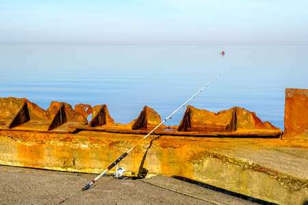 a white fishing rod hangs over a parapet and the sea is quite calm Standard-Bild
