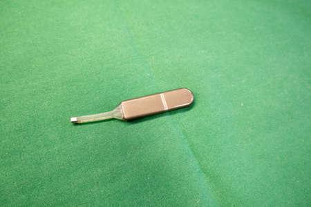 an explanted medical event recorder for recording cardiac arrhythmias lies on a green surgical drape Standard-Bild