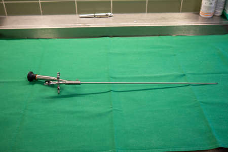 a rigid uretheroscope for the examination of ureters lies on a green surgical drape