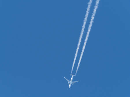 an airplane flies in the blue sky and draws white vapor trails behind it