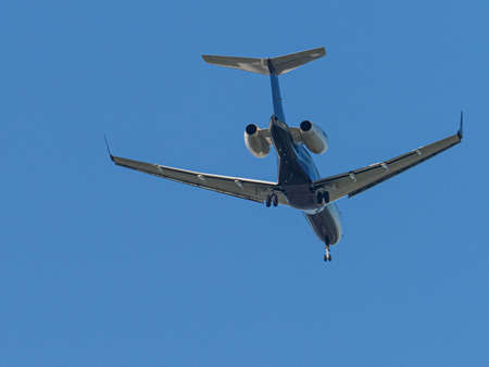 A transport plane flies in the blue cloudless sky