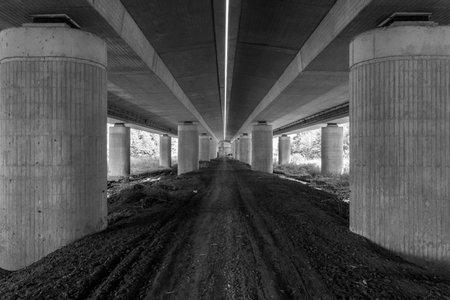 thick pillars stand under highway bridge