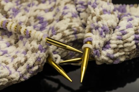 handicraft and needlework concept - close up of knitting needles and balls of yarn with unfinished scarf