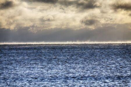 Winter on lake Michigan.On the horizon rising steam of warmer water.