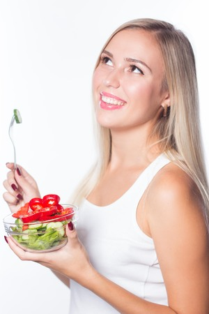 staying fit: Young beautiful woman eats vegetable salad. Healthy eating. To be in shape. Stock Photo