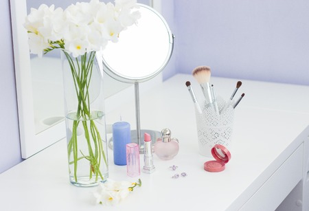 Cosmetics and a bouquet of flowers on the dressing table.