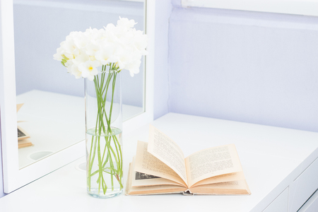 Cozy picture. Bouquet of white flowers in a vase and a book on a white table. Stockfoto