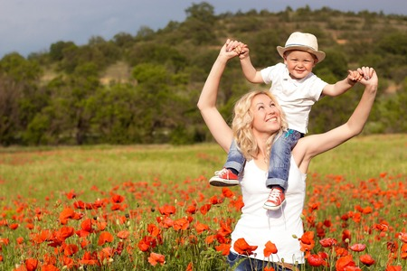 child protection: Beautiful family walking on the poppy field. Happy mother and son. Stock Photo